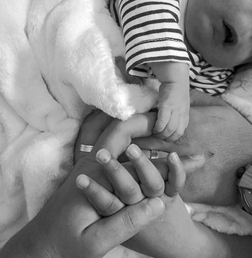 Rodrigo tiene il dito di Marlene, che ha la mano su quella di David, il padre